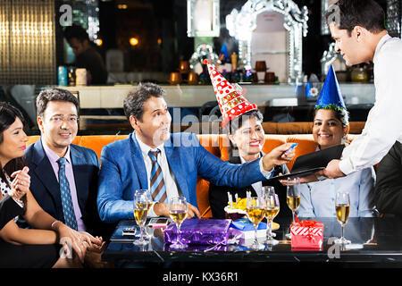 Gruppe Unternehmer, Unternehmerinnen Geburtstag Kellner unter Zahlung ec-Karte Hotel - Stockfoto
