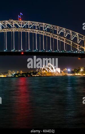 Nacht Panorama auf den Hafen von Sydney, Australien. Stadtbild bei Nacht, Australische Flaggen auf die Harbour Bridge, - Stockfoto