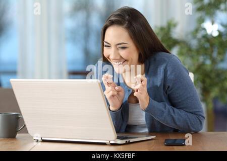 Happy hoffnungsvollen Mädchen die Daumen auf die Überprüfung der Inhalte in einem Laptop zu Hause - Stockfoto
