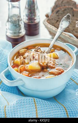 Suppe mit Hähnchen und Gemüse mit Pilzen und Tomaten in einer blauen Terrine mit Griffen auf einem Tisch mit blauem - Stockfoto