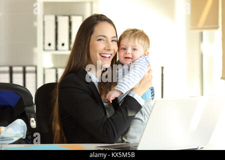 Portrait Of Happy berufstätige Mutter mit ihrem Baby und Kamera im Büro - Stockfoto
