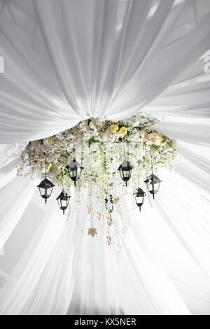 Kronleuchter aus Rosen und weißen Blumen hängt unter dem Zelt ...