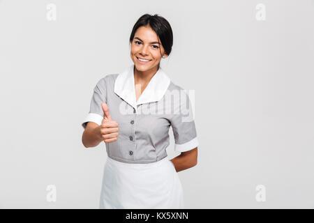 """Fröhliche brunette Haushälterin in Uniform zeigen """"Daumen hoch"""" Geste und Kamera, auf weißem Hintergrund - Stockfoto"""