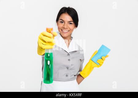 Close-up Portrait von professionellen Haushälterin in Uniform und gelbe Gummihandschuhe sprühen Sie das Reinigungsmittel - Stockfoto