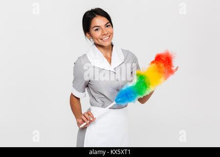 Fröhliche brunette Haushälterin in Uniform Holding bunte Duster und Kamera, auf weißem Hintergrund - Stockfoto
