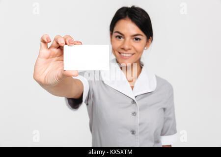 Junge attraktive femmale Haushälterin in Uniform zeigt leere Cutaway, selektiver Fokus auf Karte - Stockfoto