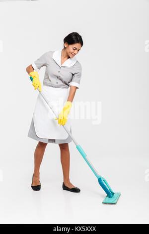 In voller Länge Porträt der jungen attraktiven Frau in Uniform Reinigung Boden mit Mop, auf weißem Hintergrund - Stockfoto