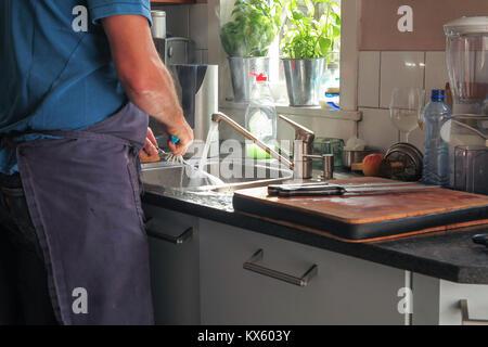 Mann Geschirr in der Küche mit Sonnenlicht auf dem Wasser - Stockfoto