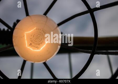Eine Glühbirne in den Vordergrund mit einem Moody Himmel im Hintergrund. - Stockfoto