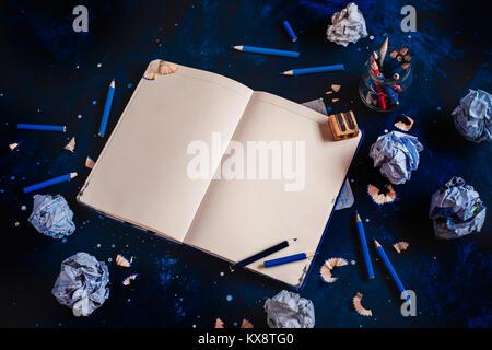 Notepad mit leeren Seiten öffnen, zerknittertes Papier Kugeln, Stifte, Notizblöcke und leere Kaffeetassen auf einem - Stockfoto