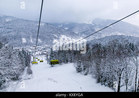 Ski Sessellift bringt Skifahrer und Snowboarder auf den Berg Skrzyczne nach starker Schneefall auf einem nebligen Wintertag in Szczyrk ski resort in Polen