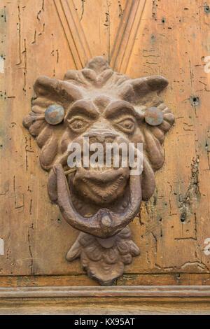 Isoliert, Nahaufnahme einer dekorativen Türklopfer, ähnelt einem Drachen Kopf, mit einem reich verzierten Griff - Stockfoto