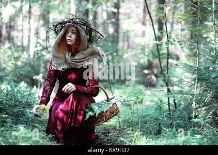 Die rothaarige Hexe hält ein Ritual mit einer Kristallkugel. - Stockfoto