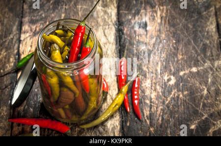 Gebeizt hot chili peppers in Glas. Auf einer hölzernen Hintergrund. - Stockfoto