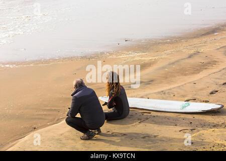 Surfer am Strand zu sitzen Weiter mit einem anderen Mann mit Blick auf das Meer am Strand von Bournemouth, Surfbrett, - Stockfoto