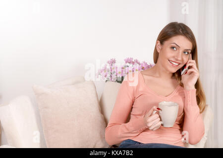 Junge Frau auf dem Sofa sitzen und trinken Tee oder Kaffee und Gespräch per Telefon über die inländischen Hintergrund. - Stockfoto