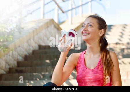 Sportliche Frau Trinkwasser nach dem Joggen. Fitness und gesunde Lebensweise Konzept - Stockfoto