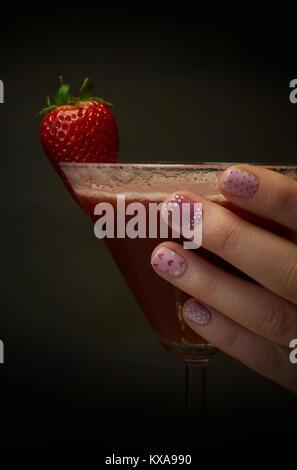 Hand mit lackierten Nägel mit einem Strawberry Daiquiri - Stockfoto