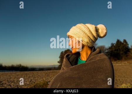 Junge Frau sitzend in gestrickt hat und in der Decke eingewickelt, während nach in Discovery Park, Seattle, Washington - Stockfoto