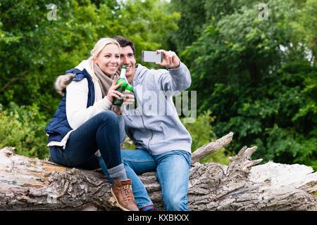 Frau und Mann trinkt Bier unter selfie beim Wandern - Stockfoto