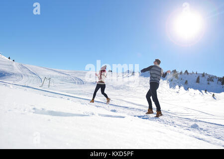 Paare, die Spaß bergab laufen - Stockfoto