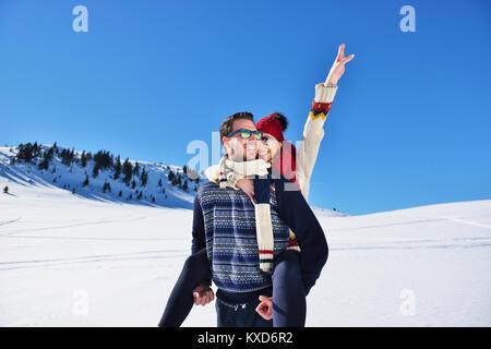 Ein junges Paar, das Spaß im Schnee. Glückliche Menschen am Berg, piggyback Ride zu sein lächelndes Freundin. - Stockfoto