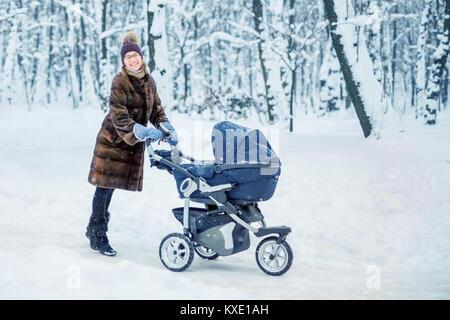 Junge schöne Mutter in einem pelzmantel Tanzen beim Spaziergang mit einem Kinderwagen in einem Stadtpark im Winter. - Stockfoto