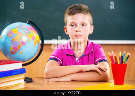 Niedliche fleißige Junge sitzt im Klassenzimmer vor Tafel - Stockfoto