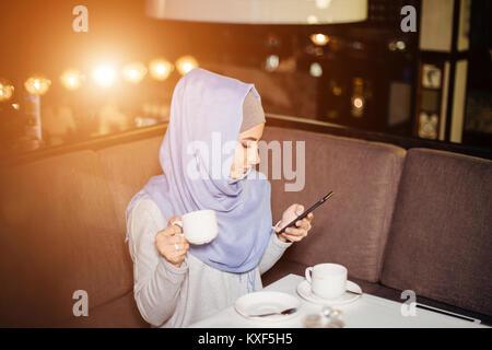 Muslimische Frau SMS-Nachrichten auf einem Mobiltelefon im Cafe Stockfoto