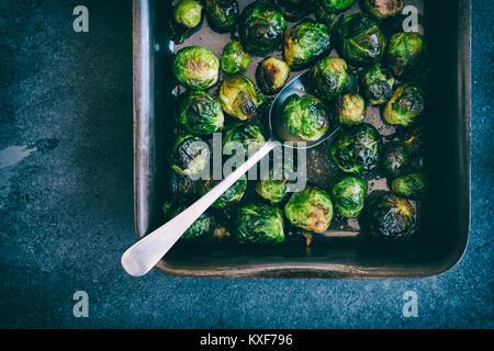 Brassica oleracea. Gerösteter Rosenkohl in einem Backblech mit Löffel auf einer Schiefertafel Hintergrund. Vintage - Stockfoto