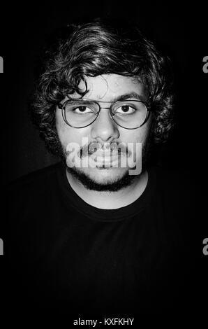 Moody dunklen Porträt eines jungen Mannes mit Escobar Brillen schauen direkt in die Kamera auf schwarzem Hintergrund. - Stockfoto