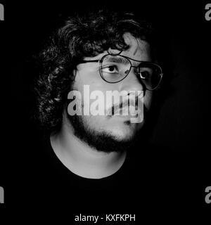 Porträt eines jungen Mannes mit Brillen, die Sie suchen, auf schwarzem Hintergrund. - Stockfoto