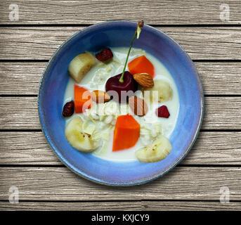 Frühstück von Soja Milch mit Kirsche, Nuß, almondand Beeren Mix mit Bananen und Papaya in kleinen Schüssel über - Stockfoto