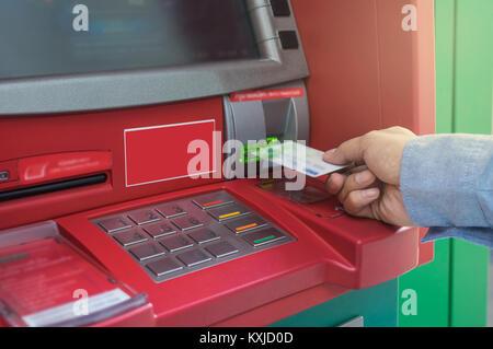 Nahaufnahme der männlichen Hände über und mit ATM Card in Bank Maschine für das Geld, Business Technology banking - Stockfoto