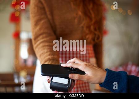 Kunden, Cafe, das kontaktlose Bezahlen mit dem Mobiltelefon - Stockfoto