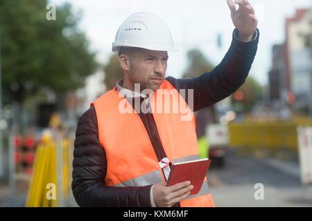 Straße Ingenieur Signalisierung mit Hand und hält digital Tablet - Stockfoto