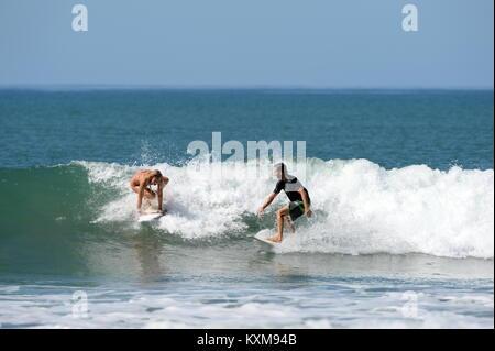 Surfen mit einem Freund in Costa Rica (Sequenz 1) - Neu engagiert Denise und Kris teilen eine Welle zusammen bei - Stockfoto