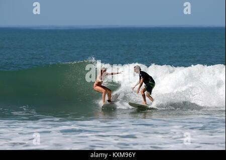 Surfen mit einem Freund (Sequenz 3) in Costa Rica - Neu engagiert Denise und Kris teilen eine Welle zusammen bei - Stockfoto