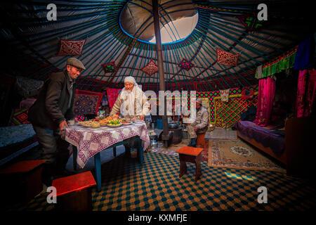 Ländliche alte Paar Mongolischen kasachischen Eagle Hunter Familie das Abendessen serviert Tabelle innerhalb Ger - Stockfoto