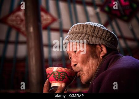 Ländliche alte mongolische Kasachischen Eagle Hunter schlürfen Tee trinken in Ger - Stockfoto