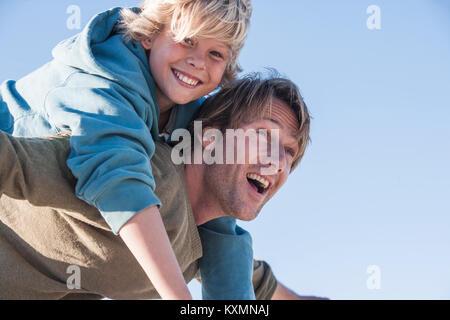 Vater die lächelnde junge auf zurück - Stockfoto