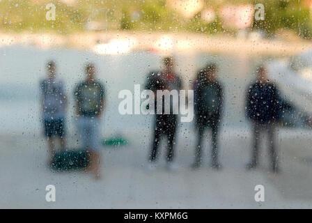Durch ein Fenster in Wassertropfen und Kondensation bei einer Gruppe von fünf Personen mit Gepäck abgedeckt - Stockfoto