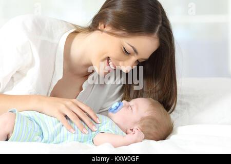 Porträt eines stolzen Mutter mit ihrem Baby beim Schlafen in einem Bett - Stockfoto