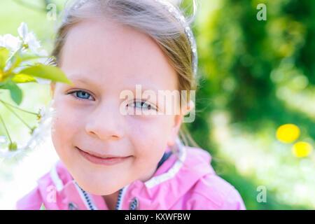 Kleine lachende Mädchen in rosa Jacke halb geschlossenen Augen auf einem Frühling Hintergrund mit blühenden Blumen - Stockfoto