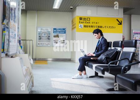 Unternehmer tragen Anzug sitzen am Bahnhof, Arbeiten am Laptop. - Stockfoto
