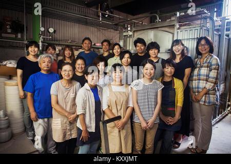 Gruppenbild der Mitarbeiter eines japanischen Porzellan Werkstatt stand vor der Brennofen, in die Kamera lächeln. - Stockfoto