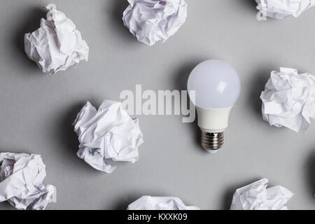 Inspiration und Phantasie Konzept. Glühbirne mit weißen zerknittertes Papier Dokumente - Stockfoto