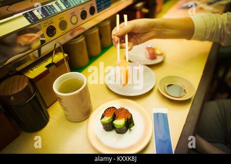 Hohen Winkel in der Nähe der Person essen in einer Sushi-Bar mit Sushi Zug, Kaiten-zushi. - Stockfoto