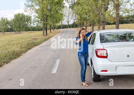 Junge Frau ruft zur Unterstützung neben einer Panne mit dem Auto auf der Seite einer Straße geparkt - Stockfoto