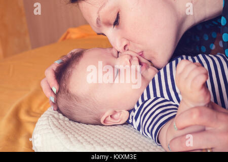 Bild einer liebenden Mutter küssen ihr Baby Sohn im Schlafzimmer - Stockfoto